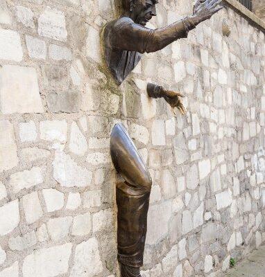 Männerskulptur durch Wand
